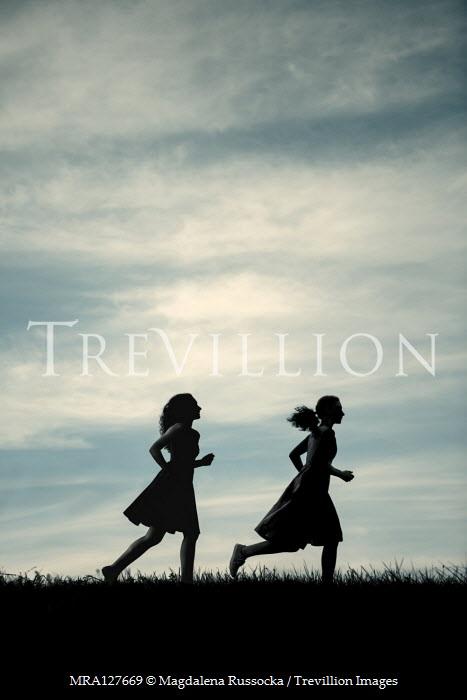 Magdalena Russocka two girls running in field at dusk Women