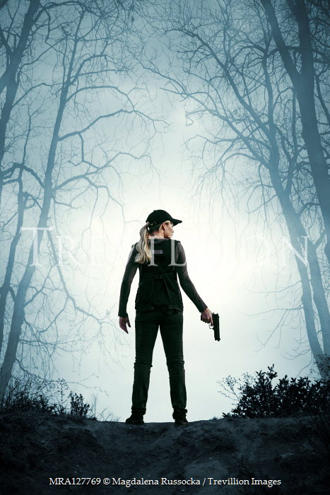 Magdalena Russocka modern woman with gun standing in woods