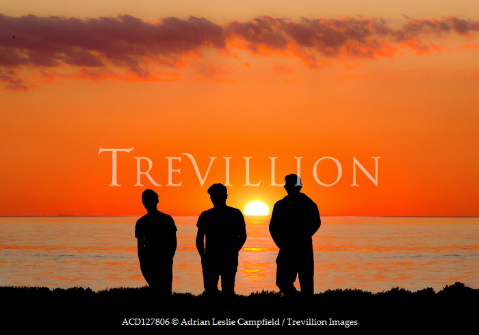 Adrian Leslie Campfield Silhouette of teenage boys by sea at sunset