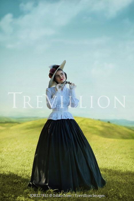 Ildiko Neer Victorian woman tying ribbon on meadow