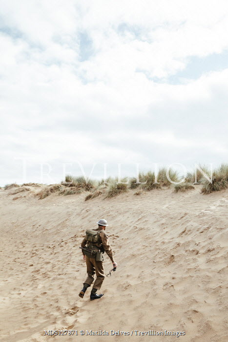 Matilda Delves WWI soldier walking on sand dunes