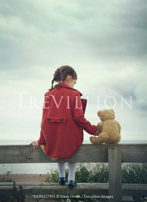 Mark Owen LITTLE GIRL SITTING ON BENCH WITH TEDDY BY SEA Children