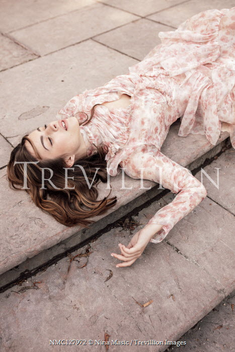 Nina Masic WOMAN LYING OUTSIDE ON STEPS IN PINK FLORAL DRESS Women