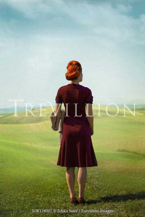 Ildiko Neer Vintage woman standing in meadow with coat