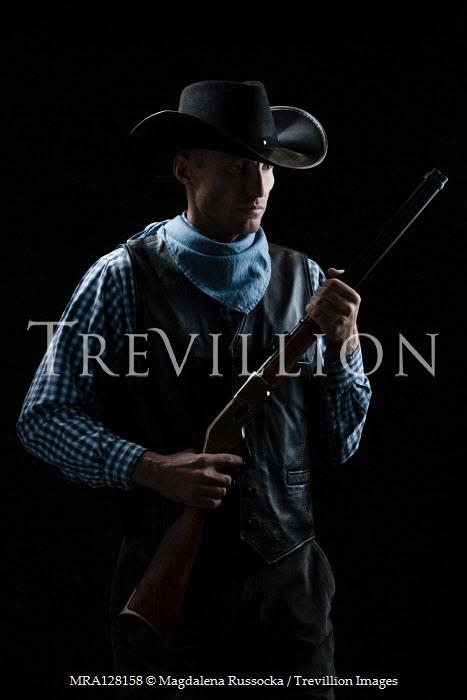 Magdalena Russocka man in cowboy hat holding rifle inside