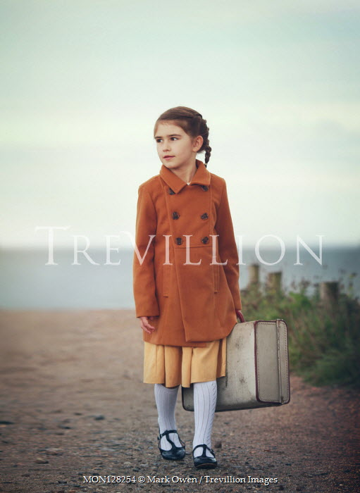 Mark Owen Girl with suitcase walking on path
