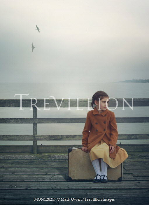 Mark Owen Girl with suitcase sitting on pier