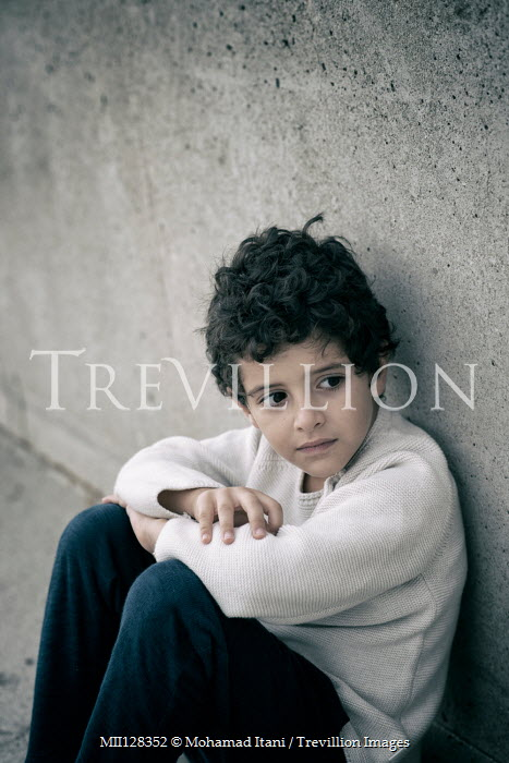 Mohamad Itani Boy sitting by concrete wall