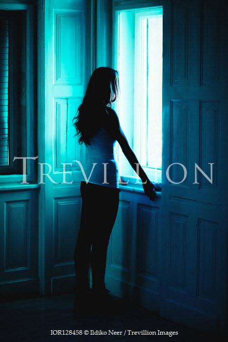 Ildiko Neer Modern woman standing by window in dark room