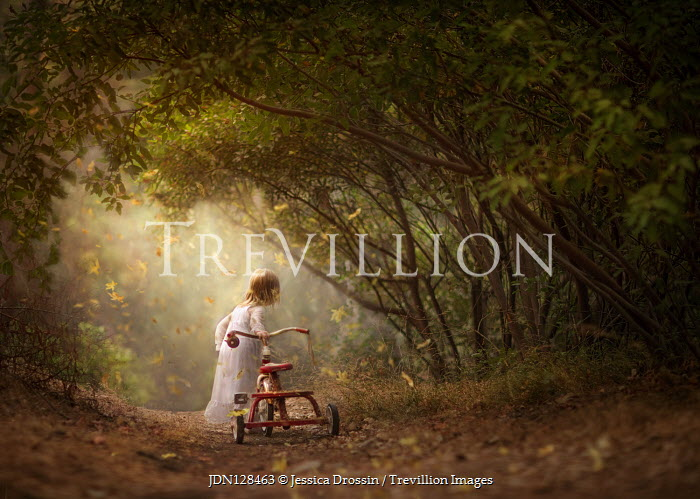 Jessica Drossin Girl walking tricycle in forest
