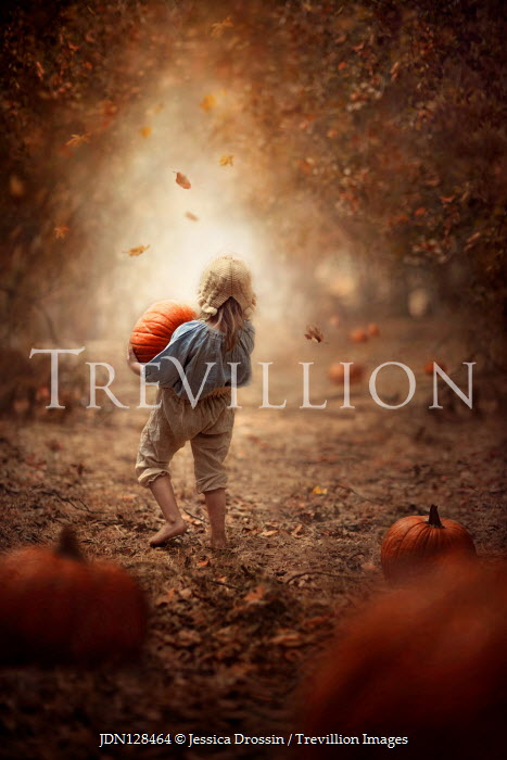 Jessica Drossin Girl carrying pumpkin in forest