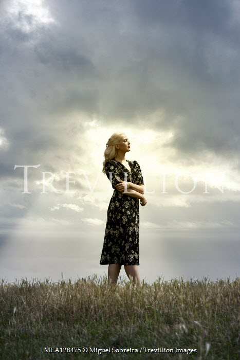 Miguel Sobreira Forties Blonde Woman Standing on Hilltop Bathed in Sunlight