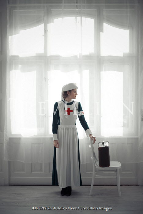 Ildiko Neer Wartime nurse standing by window
