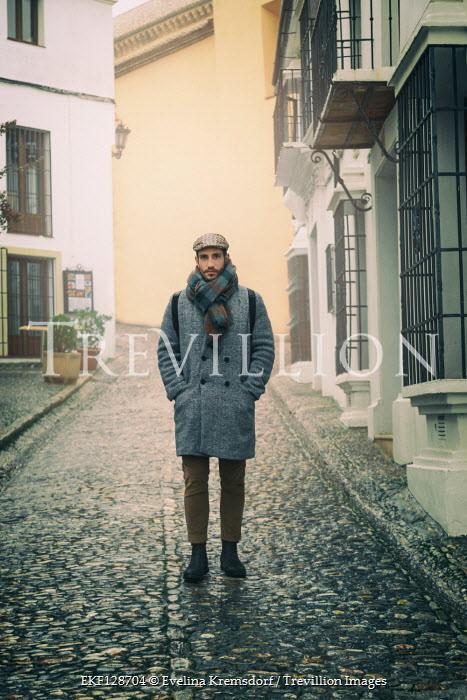 Evelina Kremsdorf MAN WITH COAT STANDING IN COBBLED STREET Men