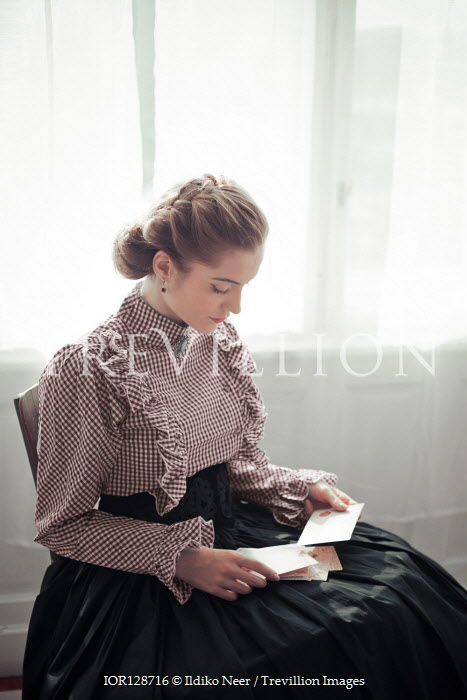 Ildiko Neer Victorian woman sitting and reading postcards at window Women
