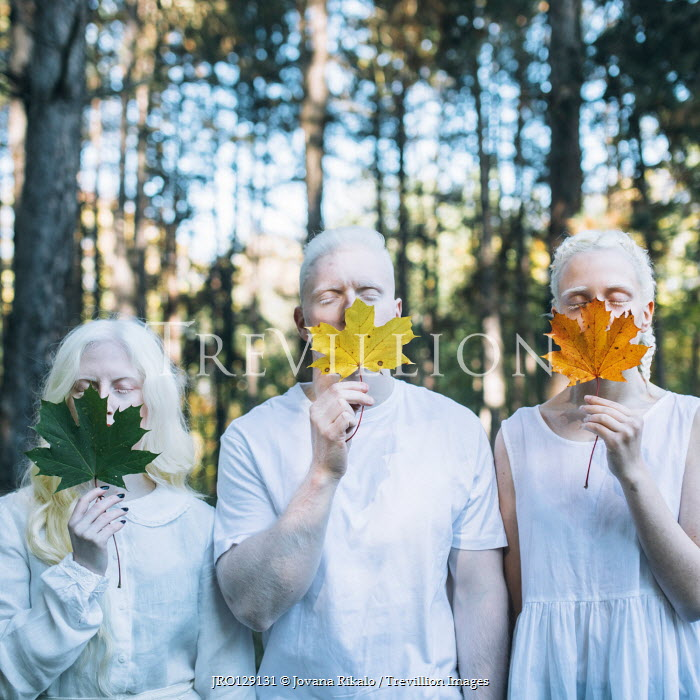 Jovana Rikalo Albino man and women holding leaves in forest