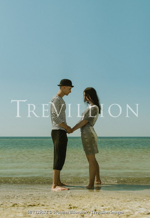 Svitozar Bilorusov Teenage couple holding hands on beach