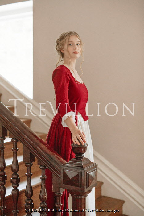 Shelley Richmond Victorian woman in red dress standing on staircase