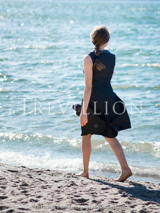 Elisabeth Ansley Woman in black dress walking on beach