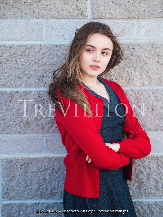 Elisabeth Ansley Young woman in red sweater by brick wall