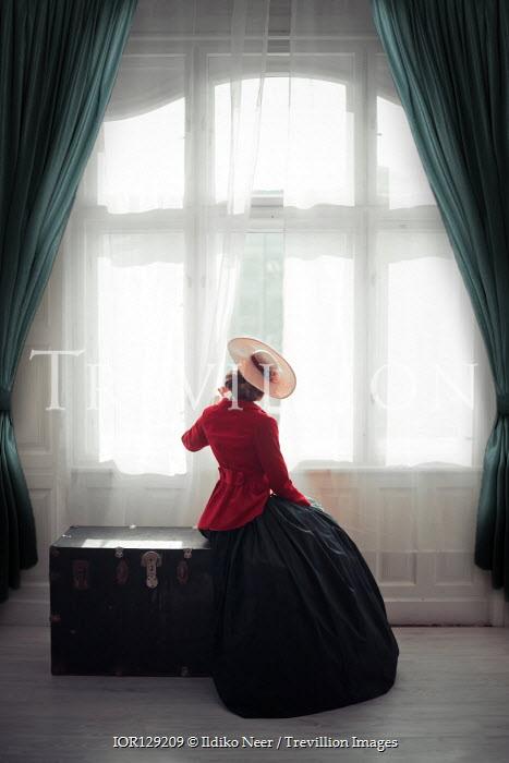 Ildiko Neer Victorian woman sitting on trunk by window