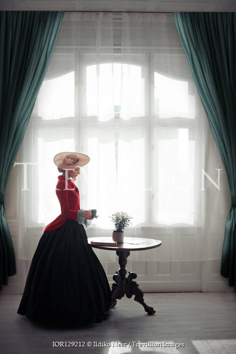 Ildiko Neer Victorian woman holding cup by window