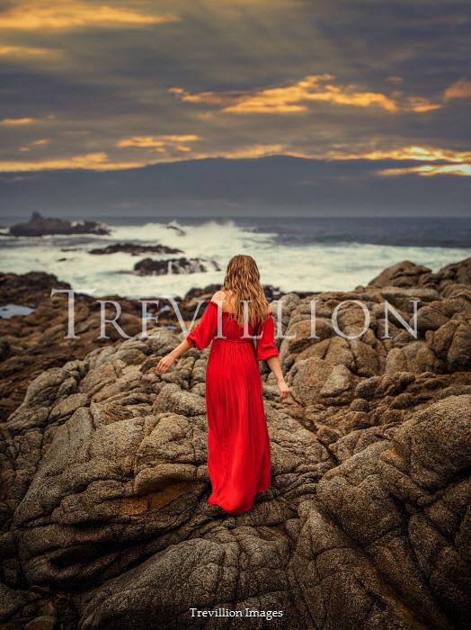 Lilia Alvarado Woman in red dress walking on rocks