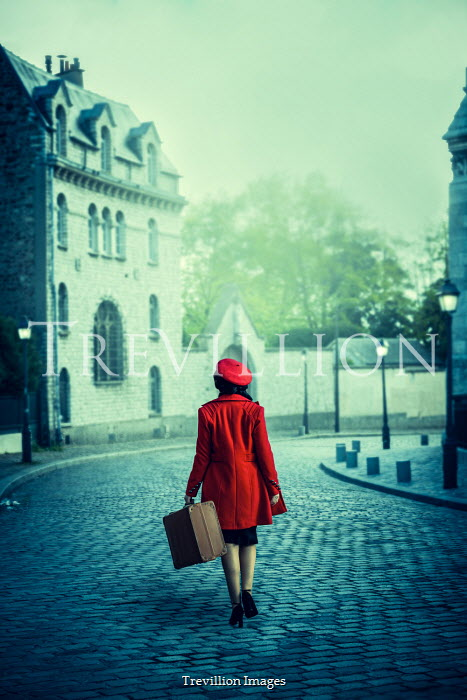 Marie Carr Woman in red beret and coat holding suitcase while walking on road