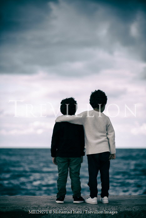 Mohamad Itani Boys standing on wall by sea