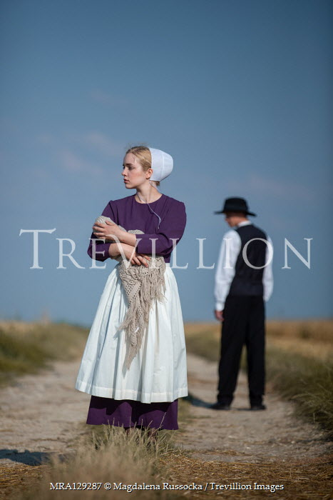 Magdalena Russocka Amish couple with baby standing in field
