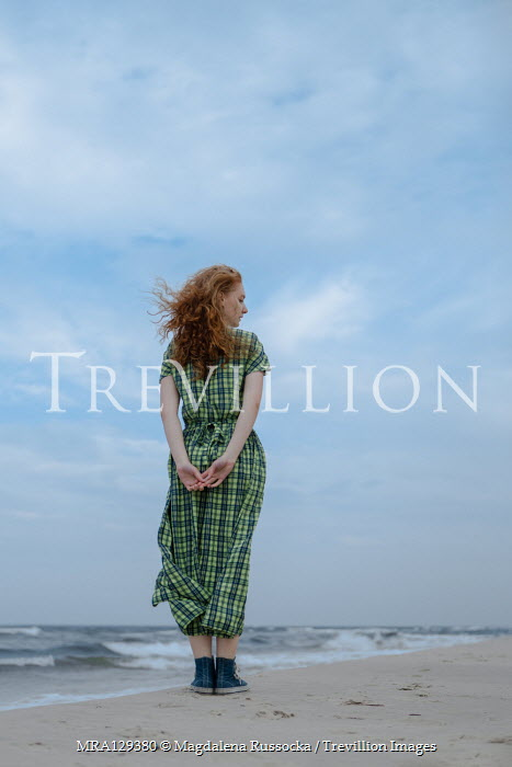Magdalena Russocka Woman in gingham dress standing on beach