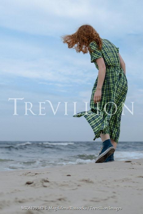 Magdalena Russocka Woman in gingham dress walking on beach