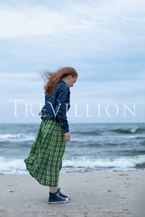 Magdalena Russocka Young woman in denim jacket and gingham dress standing on beach