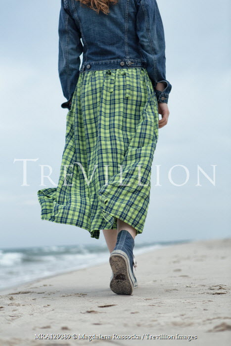 Magdalena Russocka Young woman in denim jacket and gingham dress walking on beach