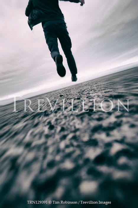 Tim Robinson Legs of man running on road
