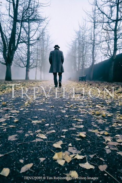 Tim Robinson Man in hat and gray coat walking in park