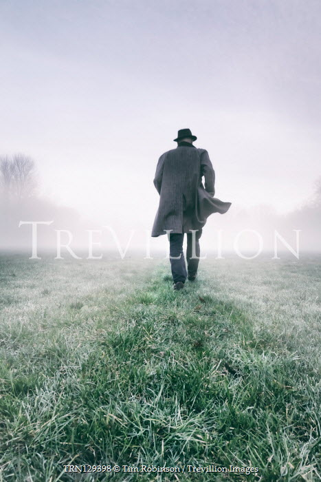 Tim Robinson Man in hat and gray coat walking in field