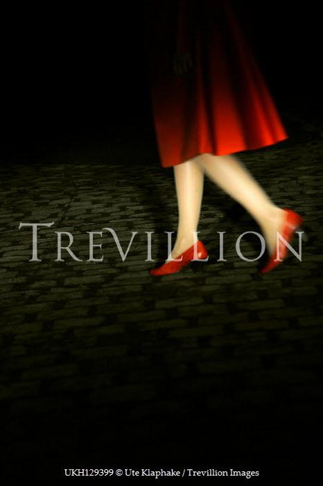 Ute Klaphake Legs of woman in red high heels walking on cobbled street