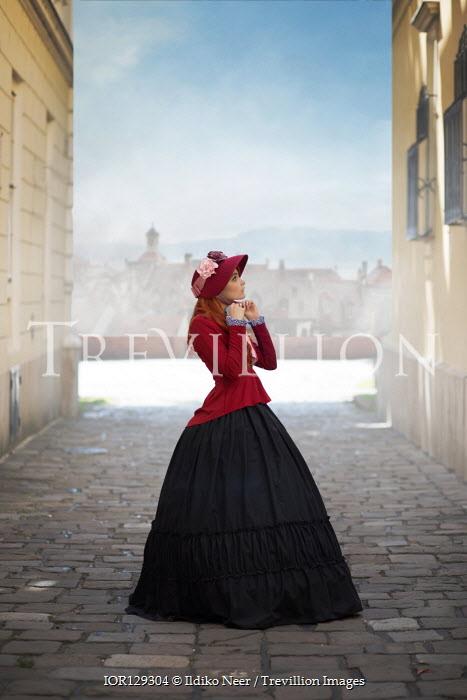 Ildiko Neer Historical woman tying bonnet on cobbled street