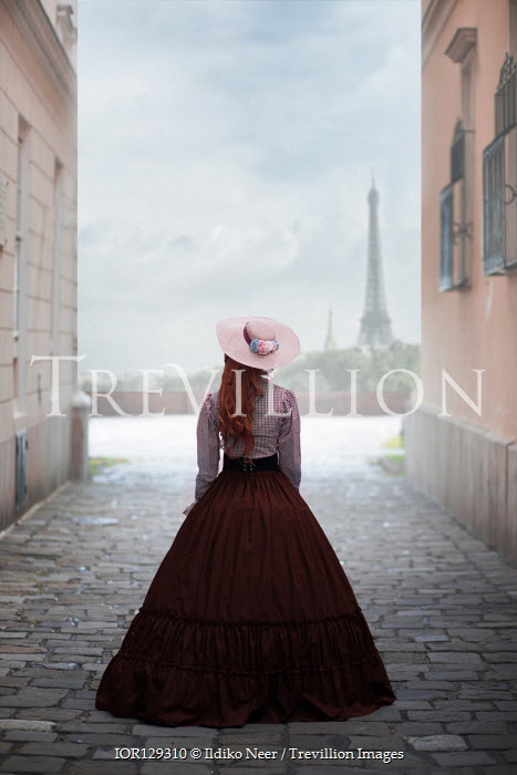 Ildiko Neer Historical woman standing on cobbled street in Paris