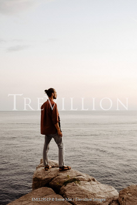 Esme Mai MAN STANDING ON ROCK WATCHING SEA IN SUMMER Men
