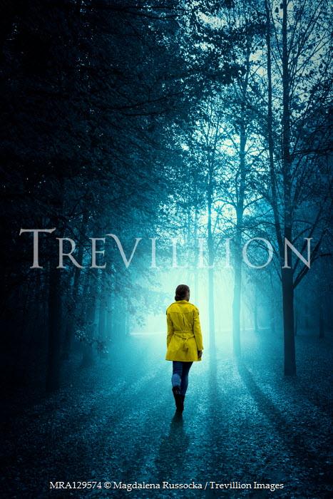 Magdalena Russocka modern woman wearing yellow jacket walking in woods