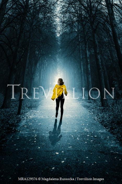 Magdalena Russocka modern woman wearing yellow jacket running in woods