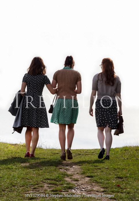 Stephen Mulcahey THREE GIRLS IN SUMMER DRESSES WALKING IN FIELD Groups/Crowds