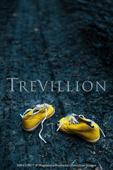 Magdalena Russocka yellow child's shoes abandoned on muddy road