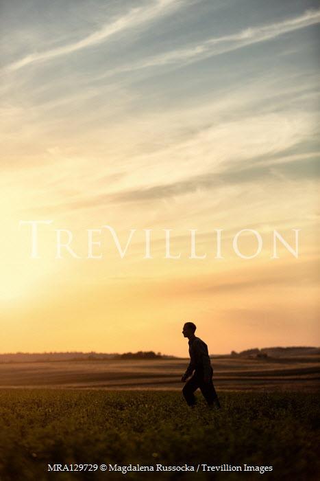 Magdalena Russocka teenage boy running in field at sunset