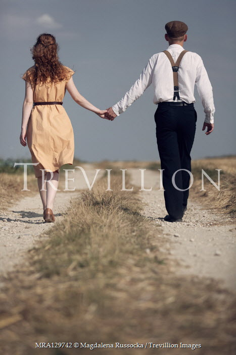 Magdalena Russocka retro couple holding hands walking on country road