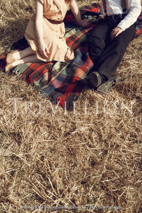 Magdalena Russocka retro couple sitting on picnic blanket in field