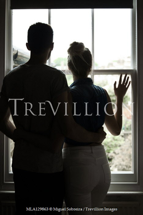 Miguel Sobreira COUPLE HUGGING BY WINDOW IN SHADOW Couples