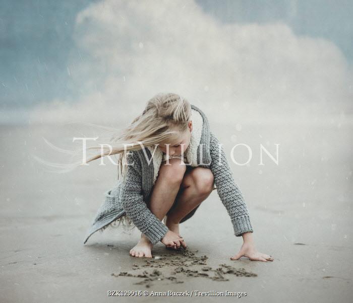 Anna Buczek YOUNG GIRL WRITING IN SAND ON BEACH Children